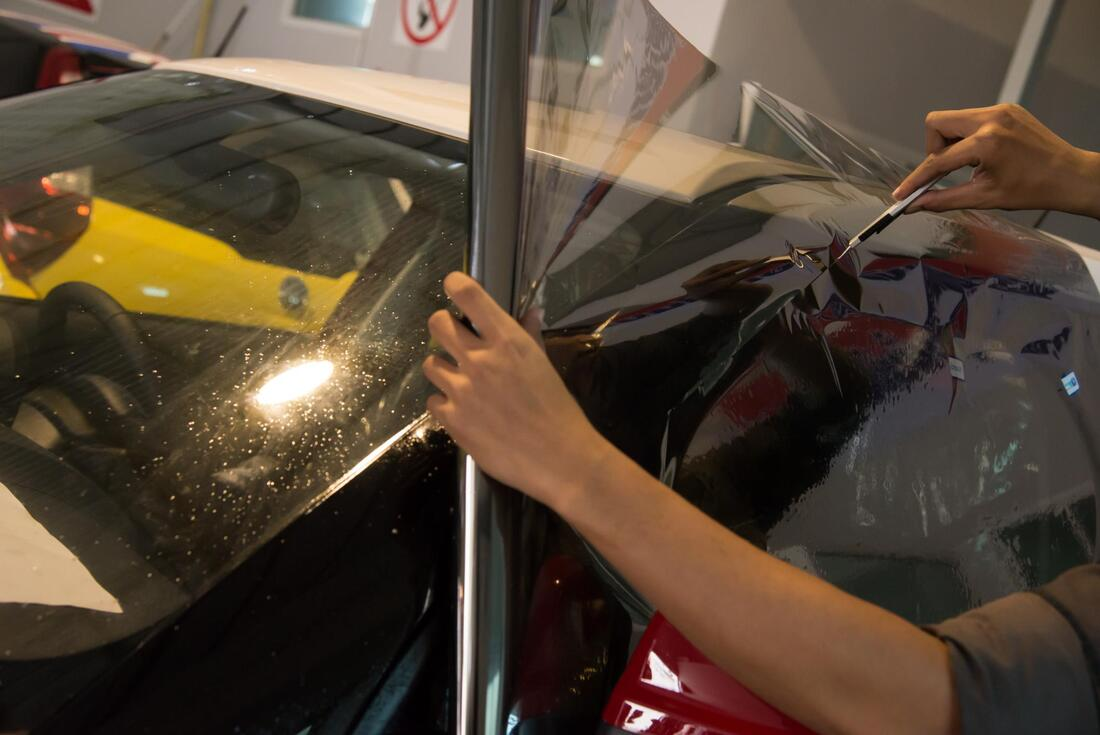 person installing window tint on a car